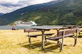 Rest Area With Table Benches And Cruise Ship On Fjord In Distance, Norwegian Tourist Destination Fla poster