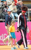 KHARKOV, UKRAINE - APRIL 21: Serena Williams with Ukrainian girl go to the court during Fed Cup tie between USA and Ukraine in Superior Golf & Spa Resort, Kharkov, Ukraine at April 21, 2012