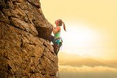 Beautiful Woman Climbing on the High Rock at Foggy Sunset in the Mountains. Adventure and Extreme Sp poster