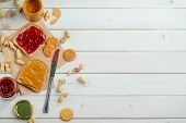 Delicious Traditional Sandwich, Jelly And Peanut Butter Jars, Crackers And Knife, Top-view. Wooden B poster