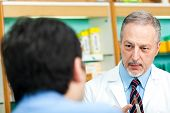 stock photo of erectile dysfunction  - Customer explaining his problems to a senior pharmacist - JPG