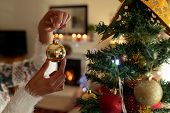 Hands of a mixed race woman in her sitting room at Christmas, holding a gold bauble and decorating C poster