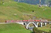SWITZERLAND - SEP 16: Glacier Express of Matterhorn-Gotthard railway passing a bridge at Furka pass