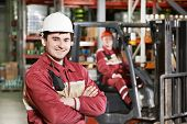 stock photo of lift truck  - young smiling warehouse worker driver in uniform in front of forklift stacker loader - JPG