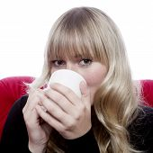 Young Blond Haired Girl Drink Cup Of Tee On Red Sofa In Front Of White Background