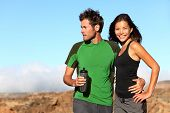 Young multicultural couple outdoors in sporty outfit. Portrait after running workout outside in moun