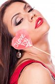 foto of fat lip  - Beautiful brunette holding heart shape lollipop with words I Love You - JPG