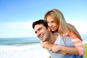 stock photo of piggyback ride  - Man giving piggyback ride to girlfriend by the sea - JPG