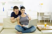 stock photo of debit card  - Couple shopping on internet paying by credit card - JPG