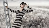 picture of spyglass  - woman stands on top of a ladder using a spyglass - JPG