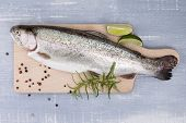 foto of peppercorns  - Trout on wooden kitchen board with colorful peppercorn fresh herbs and lime on blue wooden background - JPG