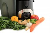 picture of juicer  - Juicer surrounded by healthy vegetables like carrots ginger and kale ready to make juice - JPG
