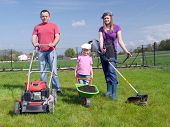 Family gardening concept, dad standing with power mower, mom holding strimmer and their cute kid posing with green barrow loaded with soil