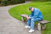Elderly Man Sitting On Park Bench