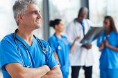stock photo of medical staff  - portrait of confident senior medical doctor in hospital - JPG