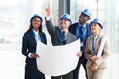 stock photo of blue-collar-worker  - group of construction workers holding blue print and discussing project - JPG