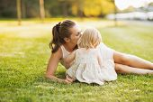 Mother Kissing Baby While Sitting On Meadow In Park