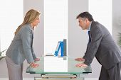 stock photo of irritated  - Two irritated businesspeople standing arguing on each side of a desk at office - JPG