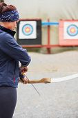Brunette preparing her bow and arrow at the archery range