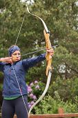 Focused brunette practicing archery in the countryside