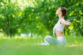 Profile of woman sitting in lotus position with outstretched arms. Concept of healthy lifestyle and