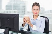 Content brunette businesswoman holding disposable cup in bright office