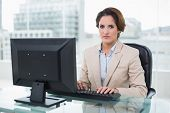 Stern businesswoman sitting looking at camera in bright office
