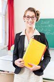 Teacher or docent in school holding folder in her hands in front of a blackboard in school class