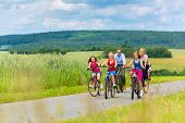 Family with three girls having a weekend excursion on their bikes on a summer day in beautiful lands