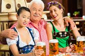 In Pub - friends in Tracht, Dirndl and Lederhosen drinking a fresh beer in Bavaria, Germany