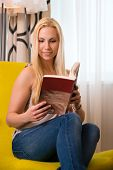 Young woman sitting on a chair in a hotel room and reading a good book, she is on vacation