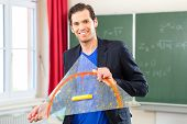 Teacher or docent in school holding a geometry triangle in front of a blackboard in school class