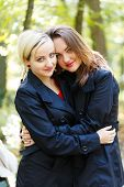 image of fraternal twins  - Two beautiful sisters in a park embracing loving each other - JPG