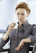 stock photo of blouse  - Young businesswoman looking at stain on her blouse made by spilling coffee on it - JPG