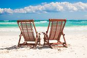 stock photo of recliner  - Beach wooden chairs for vacations and relax on tropical white sand beach in Tulum Mexico - JPG