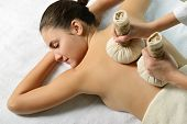 portrait of young beautiful woman in spa salon gets massage with spa herbal balls