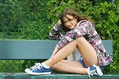 Teenager girl sit on a bench in a park