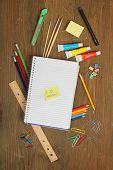 School material, pencil, rule, brushes, paper clips on a wooden table with a note book with a postite with