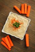 Top view of a hummus in a white container with fresh carrots