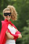 smiling blond and young woman with a mask and red super hero kit