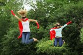 Super team of super hero girl with red cape, red gloves and black mask jumping in the air