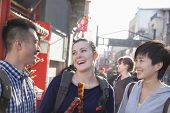 Three young people with candied haw talk on the street