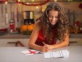 Happy Young Housewife Signing Christmas Postcards In Kitchen