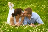 Couple On A Green Meadow Is Kissing