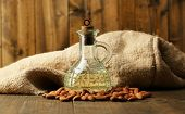 Bottle with almonds oil on color wooden background