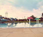 a local public pool without any people in it as sunset done with a retro vintage instagram like filt