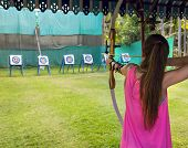 stock photo of longbow  - Archer young woman pulls the bowstring and arrow aiming at a target - JPG