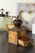 foto of coffee grounds  - Old vintage manual coffee mill or grinder with a drawer full of freshly ground coffee beans standing on an old wooden kitchen counter with a cup and saucer ready to brew a morning drink - JPG