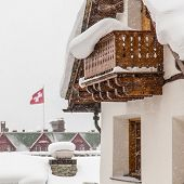 pic of chalet  - Swiss chalet during heavy snow with Swiss flag in background - JPG