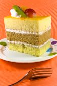 Tasty Yellow And Brown Cake With White Cream Layers And Fruit Decorations.